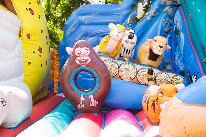 Colorful and joyful bouncing castle with different happy animal characters royalty free stock images
