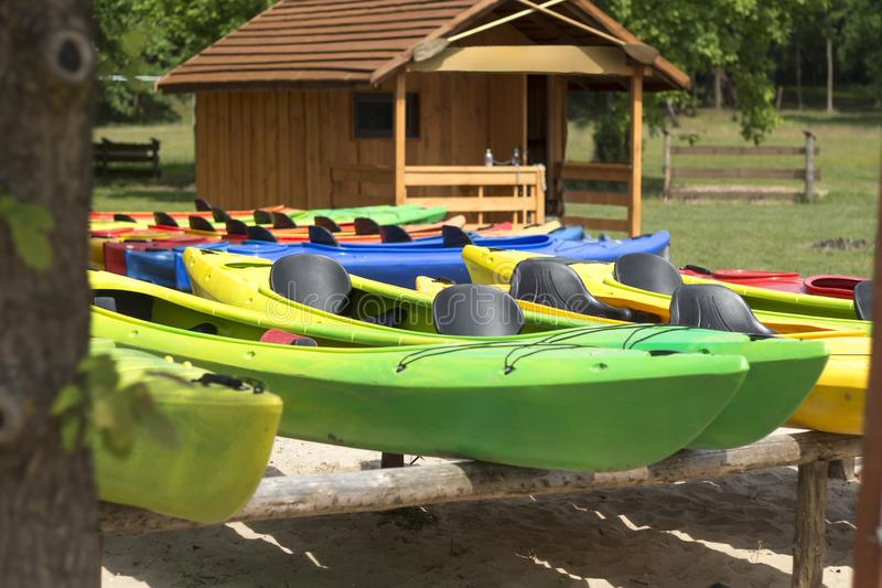 Colorful kayaks placed on racks against the background of a wooden house. Relaxing on the water. Water equipment rental. royalty free stock images