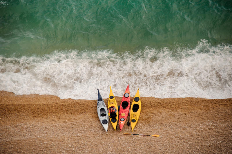 Colorful kayaks on sandy beach. royalty free stock photography