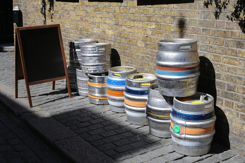 Colorful kegs of beer at the exit of a pub, on a brick wall. Picture of a street and a all with bricks and boards at the exit of a inn, showing several colorful stock photos