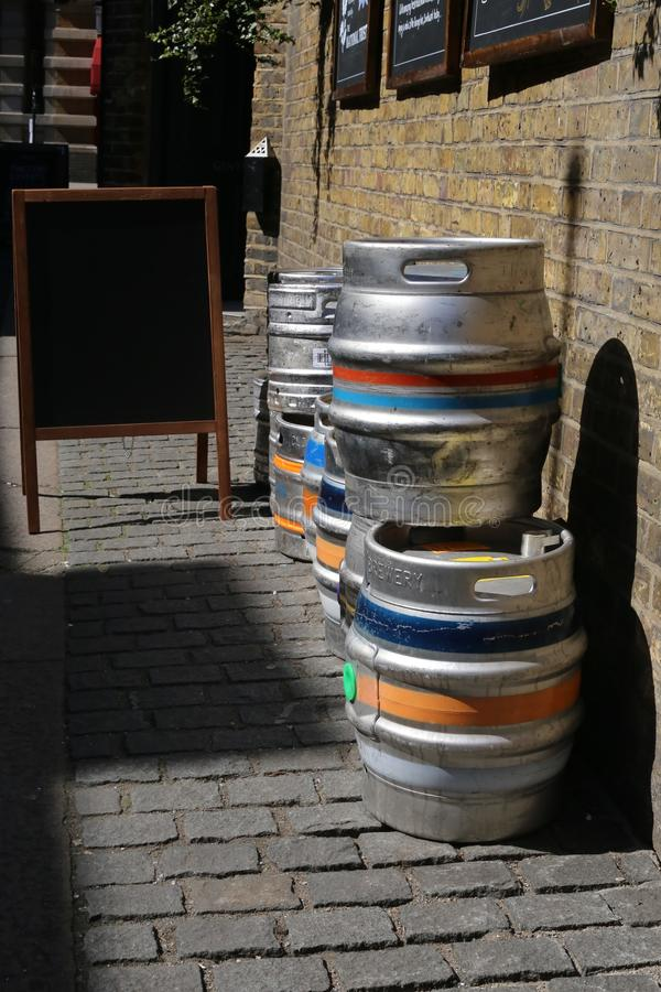 Colorful kegs of beer at the exit of a pub, on a brick wall. Picture of a street and a all with bricks and boards at the exit of a inn, showing several colorful stock photography