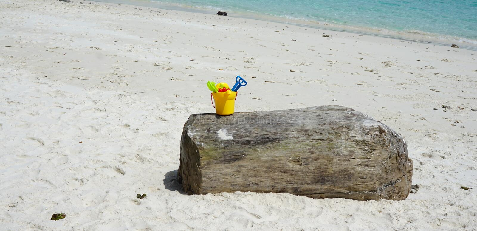 Colorful kid sand scoop toy in yellow plastic bucket on the timber log with beautiful beach background royalty free stock photos