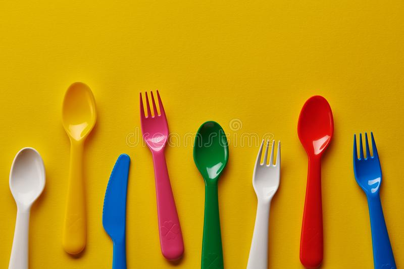 Colorful kids plastic spoons on yellow background. Many, utensils. royalty free stock photo
