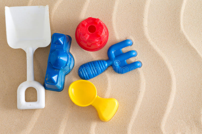 Colorful kids plastic toys at the beach. With a spade, fork , spoon and two little moulds on golden sea sand with a decorative wavy pattern and copyspace stock photography
