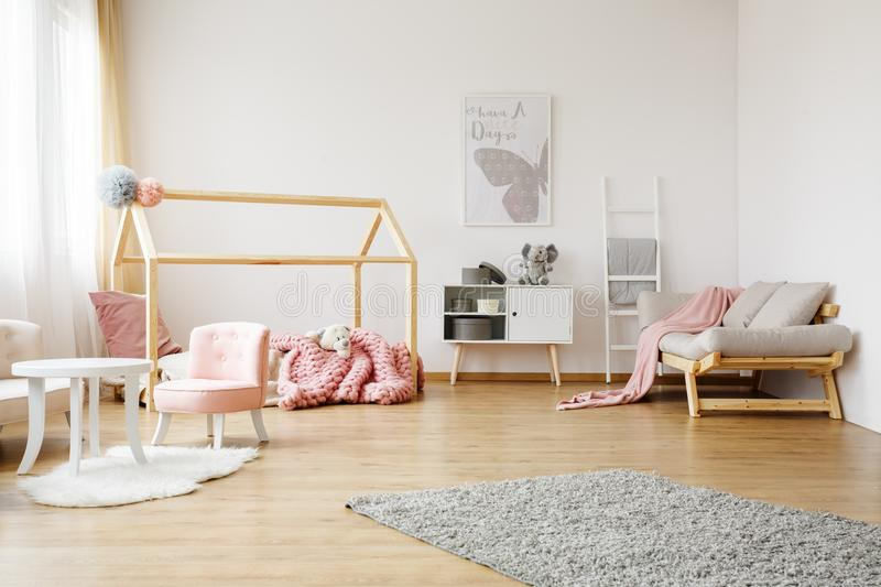 Colorful kids room. Pink blanket on grey sofa in colorful kids room with poster on white wall and ladder stock image