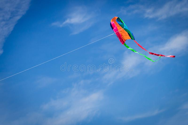 Colorful kite flying against a blue sky stock images