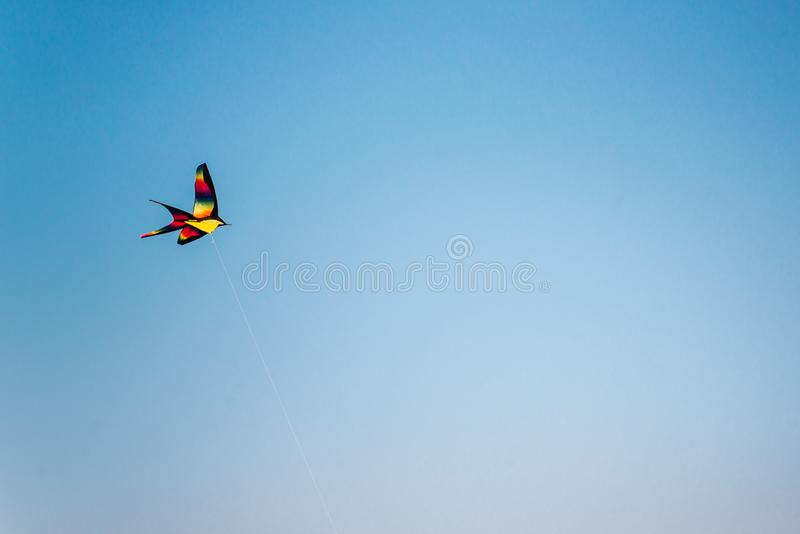 Colorful kite flying in the blue sky stock photography