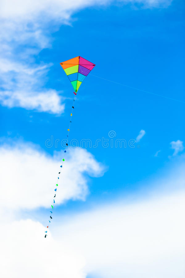 Colorful kite flying in the wind background blue stock photos
