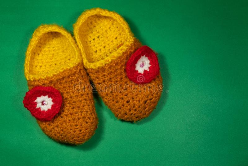 Colourful knitted Slippers on a green background. Colorful knitted baby Slippers with a red flower on a green background stock photo