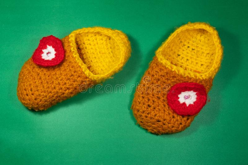 Colourful knitted Slippers on a green background. Colorful knitted baby Slippers with a red flower on a green background stock images