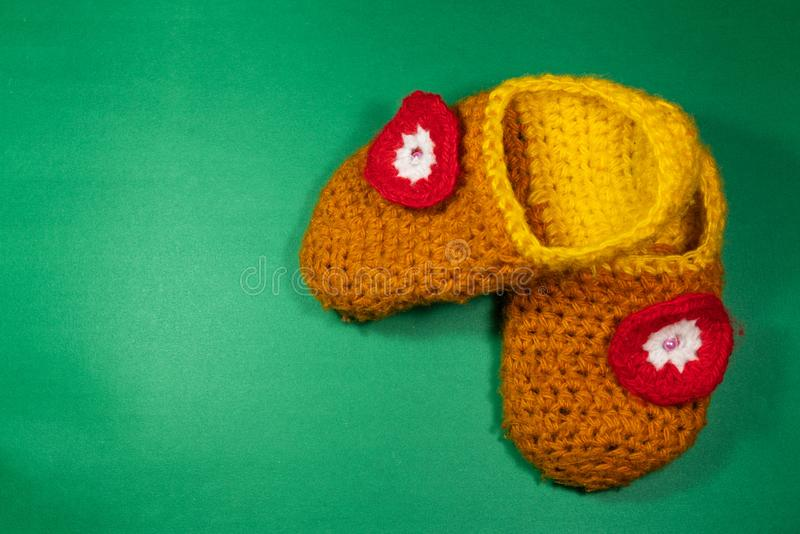 Colourful knitted Slippers on a green background. Colorful knitted baby Slippers with a red flower on a green background stock image