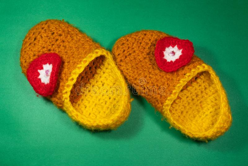 Colourful knitted Slippers on a green background. Colorful knitted baby Slippers with a red flower on a green background royalty free stock images