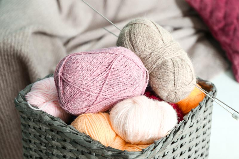 Colorful knitting yarn with needles in wicker basket indoors royalty free stock photo