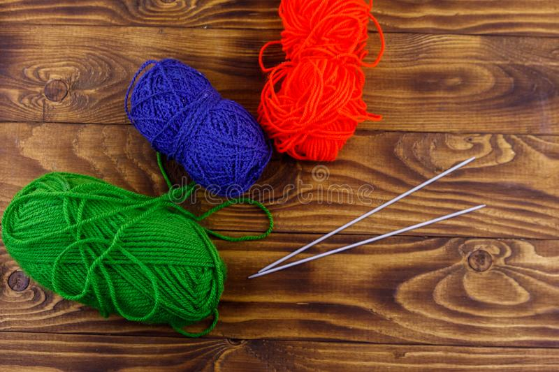 Colorful knitting yarns and knitting needles on wooden table royalty free stock photos