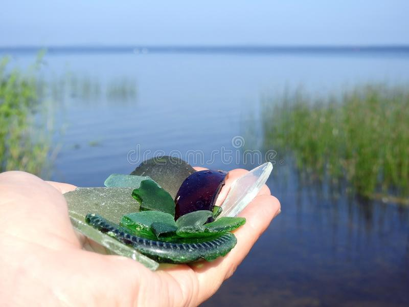 Colorful lake glass in woman hand, Lithuania royalty free stock photo
