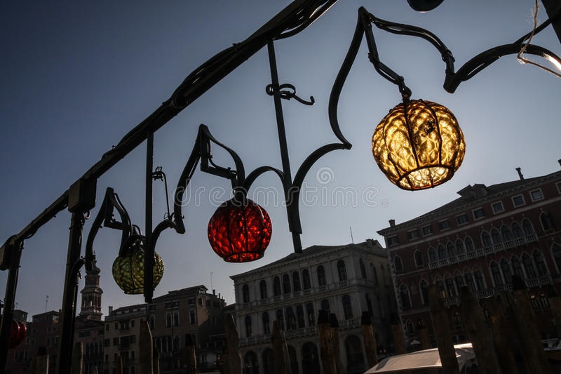 Colorful lamps on an ornate railing in Venice, Italy, with Venetian houses in the background stock photo