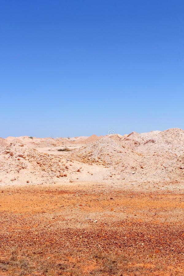 Colorful industrial landscape around mining town Coober Pedy, South Australia. Colorful desert landscape with pink hills and a blue sky around opal mining town royalty free stock photography