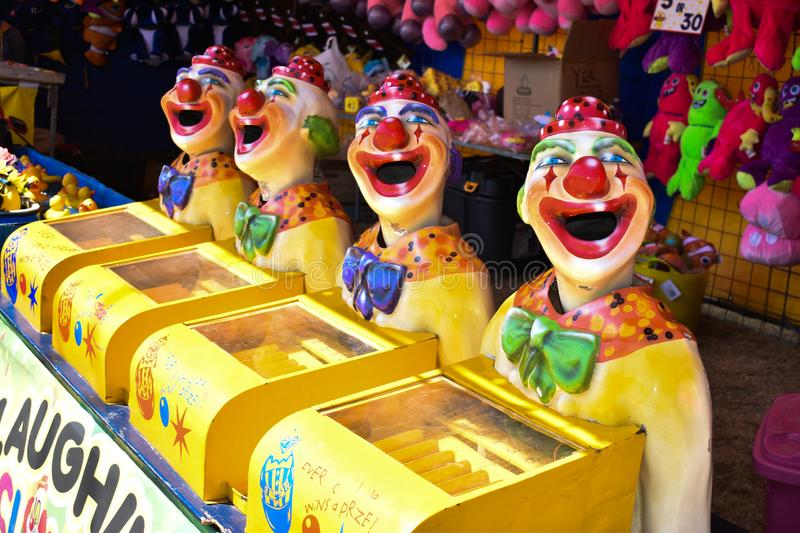 Colorful laughing clowns at a carnival. With prizes to win in the background royalty free stock images
