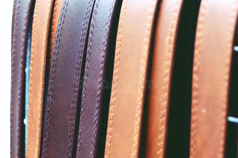 Colorful leather belts on rack close up stock photography