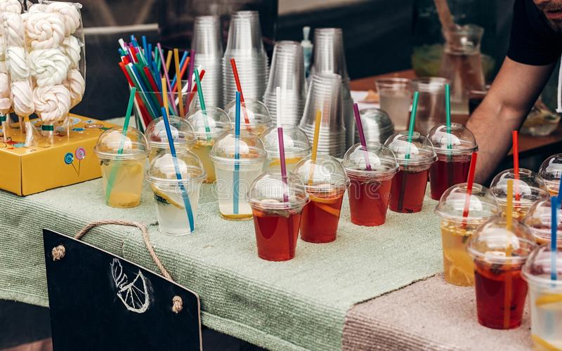 Colorful lemonades with mint and lemons and empty card on table, space for text. street food festival. drink bar at reception, ca. Tering outdoors. summer picnic stock photography
