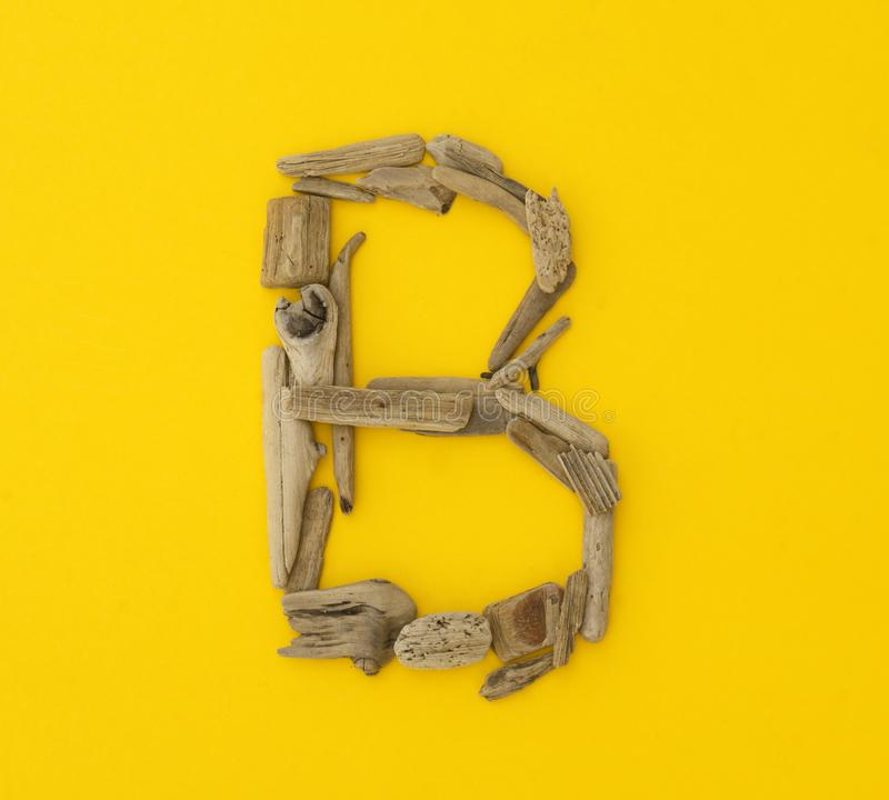 Colorful letter `b` made of wooden sticks on yellow background. royalty free stock images