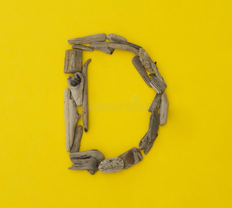Colorful letter `d` made of wooden sticks on yellow background. stock photos