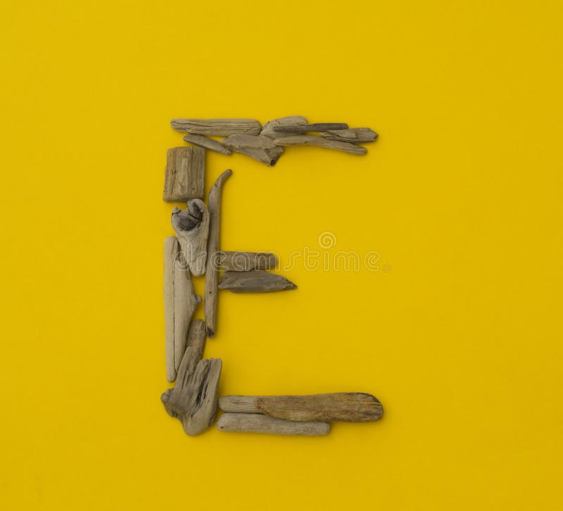 Colorful letter `e` made of wooden sticks on yellow background. royalty free stock photo