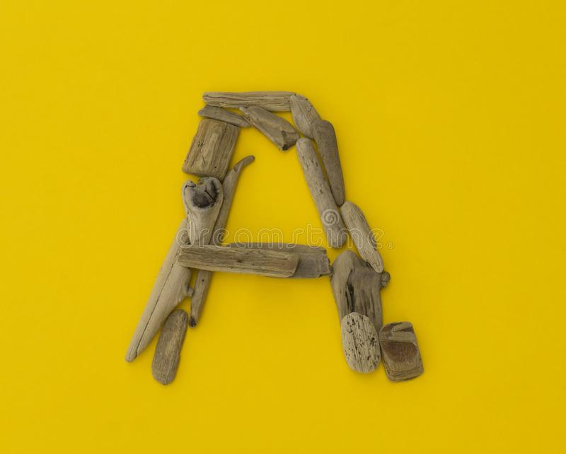 Colorful letter ` a ` made of wooden sticks on yellow background. stock photo