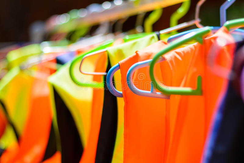 Colorful life jackets hanging on a bar. Colorful life jackets hanging on a bar, ready to be used for saving many people`s lives stock photos
