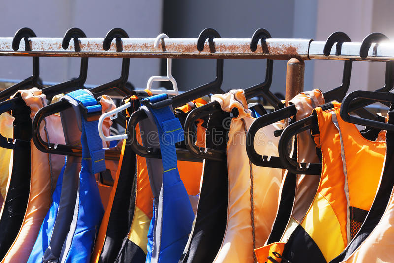 Colorful life jackets. Hanging in a row stock images
