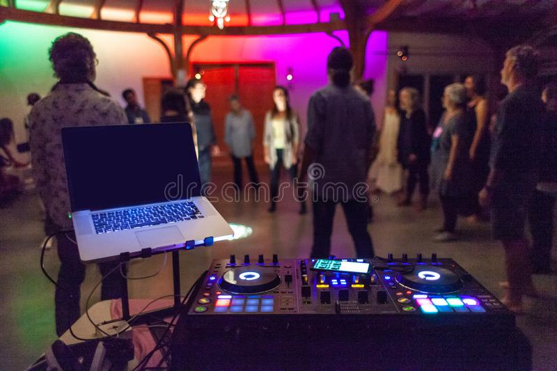 Colorful DJ mixing station in front of a blurry group of people royalty free stock image