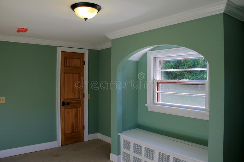 Colorful light green paint on walls of new interior home construction. Attractive light green painted walls of brand new home's construction, with arched area royalty free stock photo