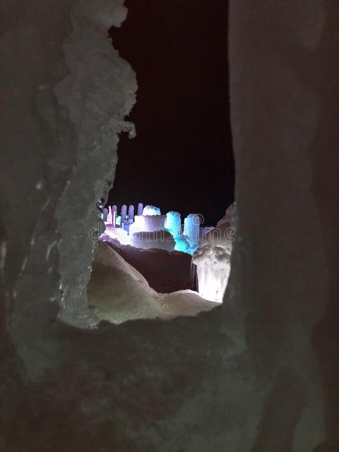 Colorful lighted icicle walls at ice castle. Looking through an opening in an ice wall you can see colorful lighted icicles in this ice castle in Lake Geneva royalty free stock photos