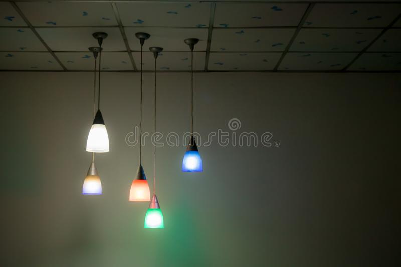 Colorful lighting lanterns hang on the ceiling in the dark room. stock photography