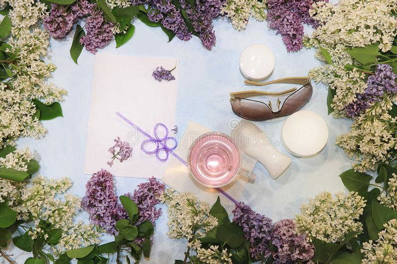 Colorful lilac branches on a blue background with juice, skin care creams, deodorant and glasses, flat lay. Preparing for summer vacation, top view with copy stock photos
