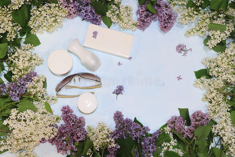 Colorful lilac branches on a blue background with juice, skin care creams, deodorant and glasses, flat lay. Colorful lilac branches on a blue background, skin stock images