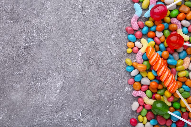 Colorful lollipop and different colored round candy on grey concrete background. Colorful lollipop and different colored round candy on grey concrete backgrond royalty free stock photos