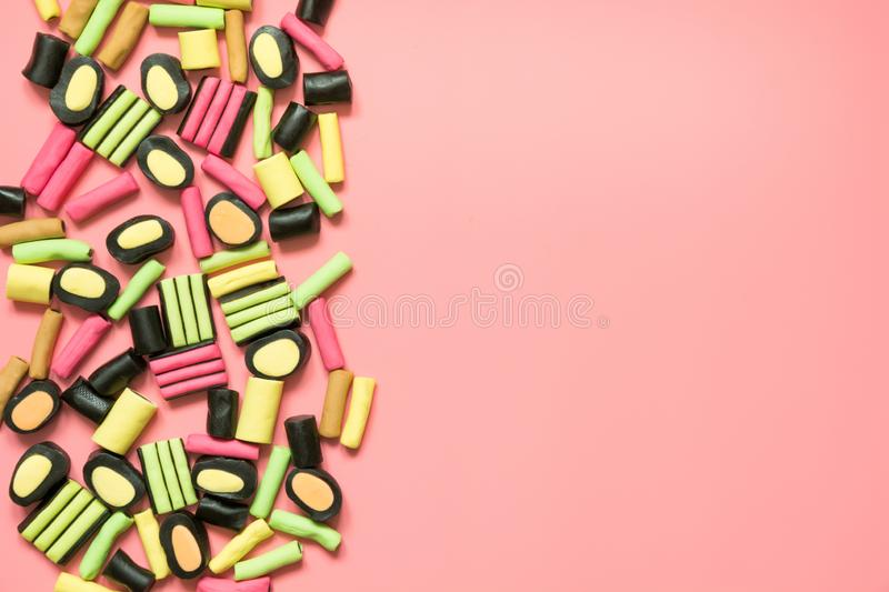 Colorful lollipop and licorice candy on pink. View from above royalty free stock images