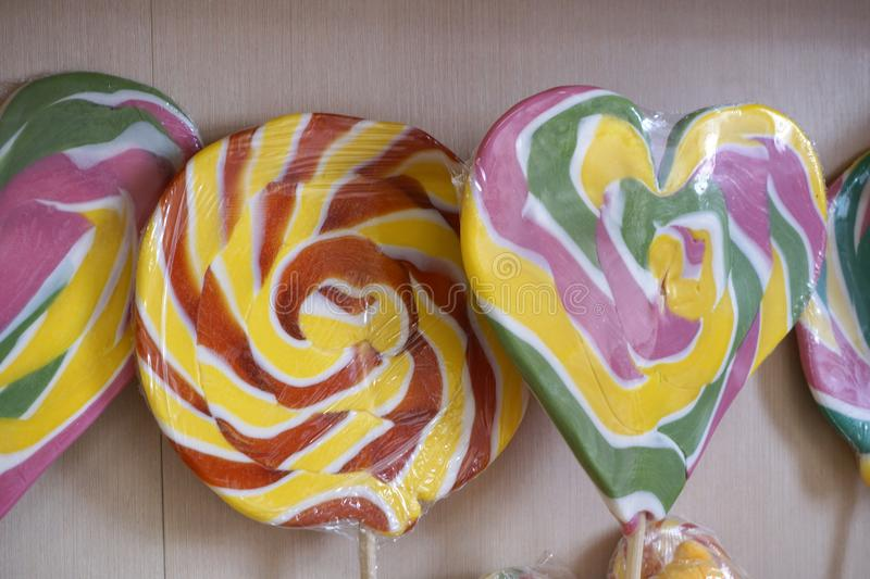 Colorful lollipop swirl of different forms on wooden stick royalty free stock photo