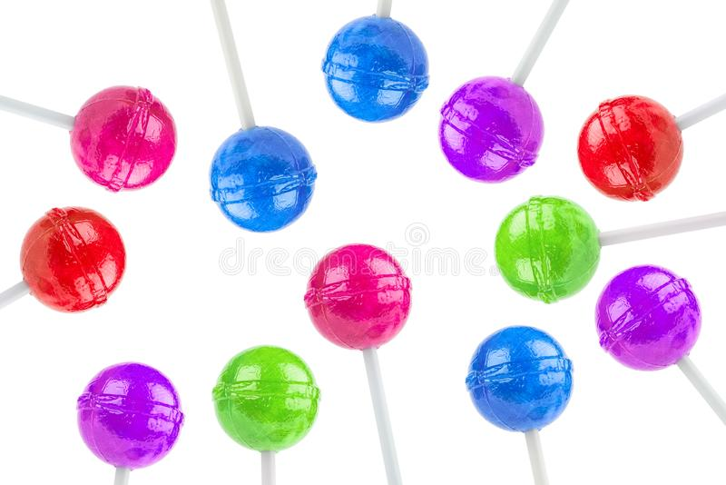 Colorful lollipops. Twelve colorful round lollipops on white sticks arrange randomly on a white background royalty free stock photos