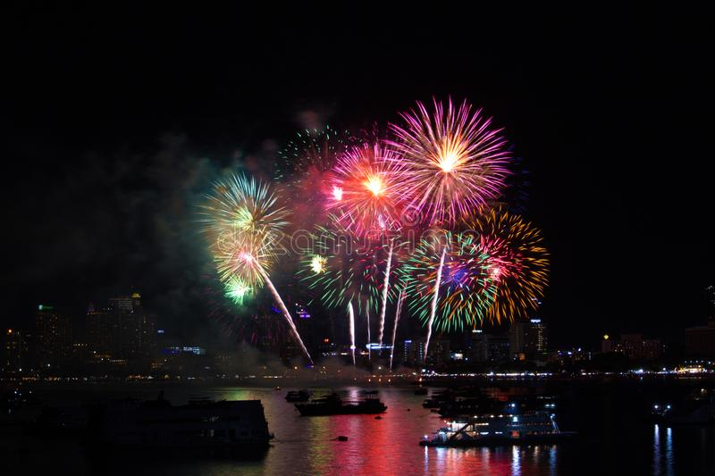 colorful long tail fireworks on beach and reflection color on water surface royalty free stock images