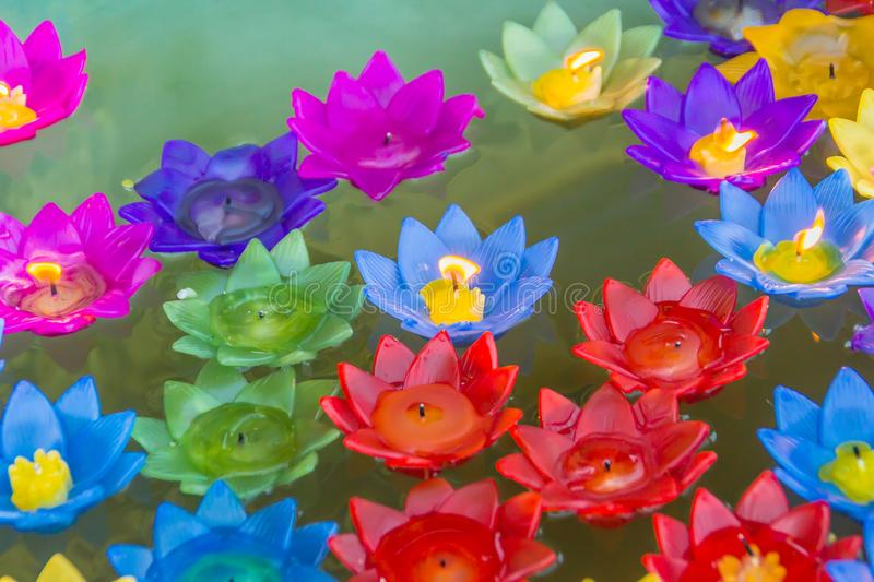 Colorful lotus flower with burning candles are floating on the water download colorful lotus flower with burning candles are floating on the water to worship the buddha mightylinksfo Images