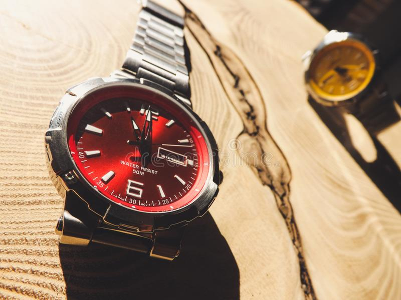 Colorful luxury watches on wood table. Red and yellow watch royalty free stock photos