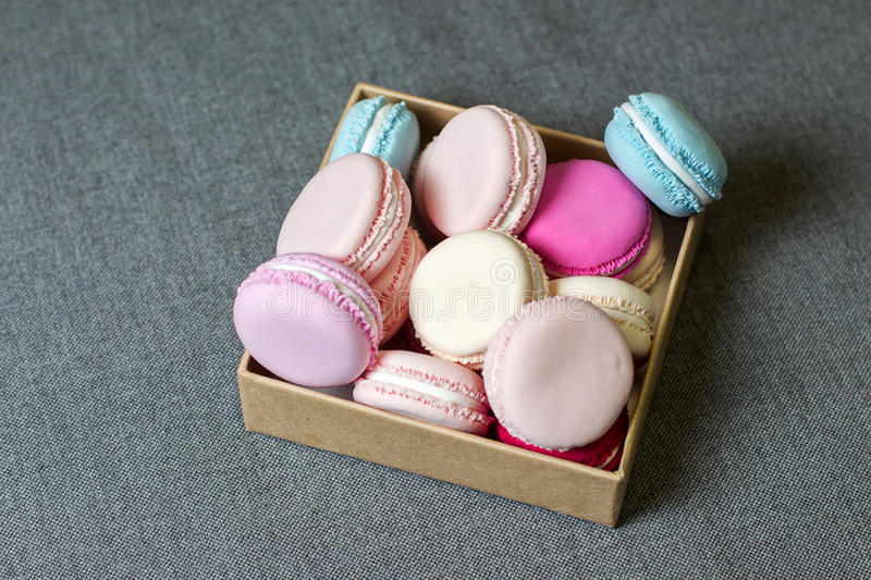 Colorful macaron in a box on the background of gray fabric royalty free stock images