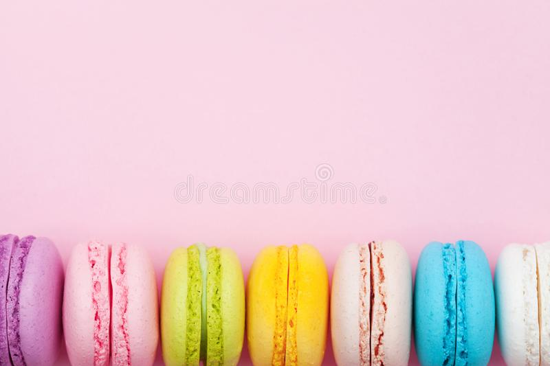 Colorful macaron or macaroon on pink pastel background top view. Flat lay composition. Colorful macaron or macaroon on pink background top view. Flat lay stock image