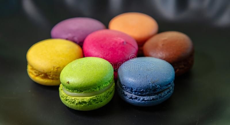 Colorful macarons on black background, close up view. Macarons pastel colors with chocolate cream on black background, close up view with details stock photography