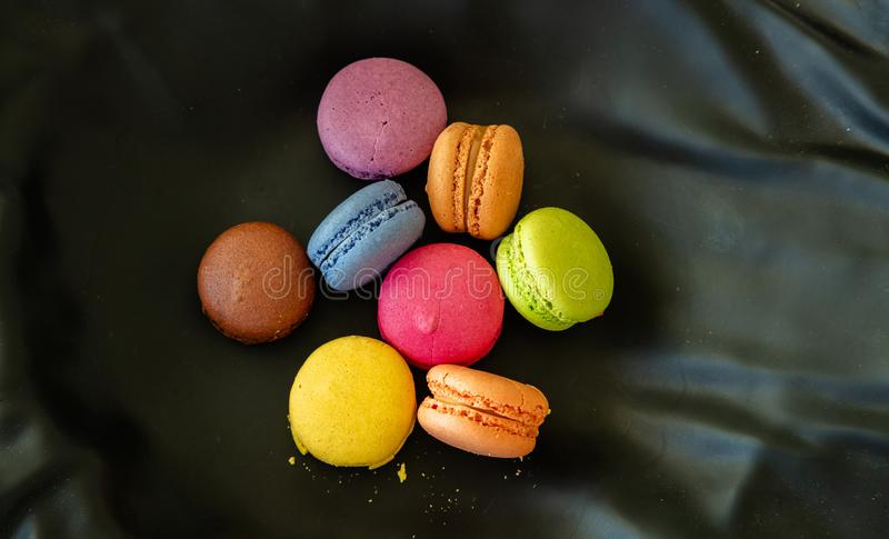 Colorful macarons on black background, close up view. Macarons pastel colors with chocolate cream on black background, close up view with details, top view royalty free stock image