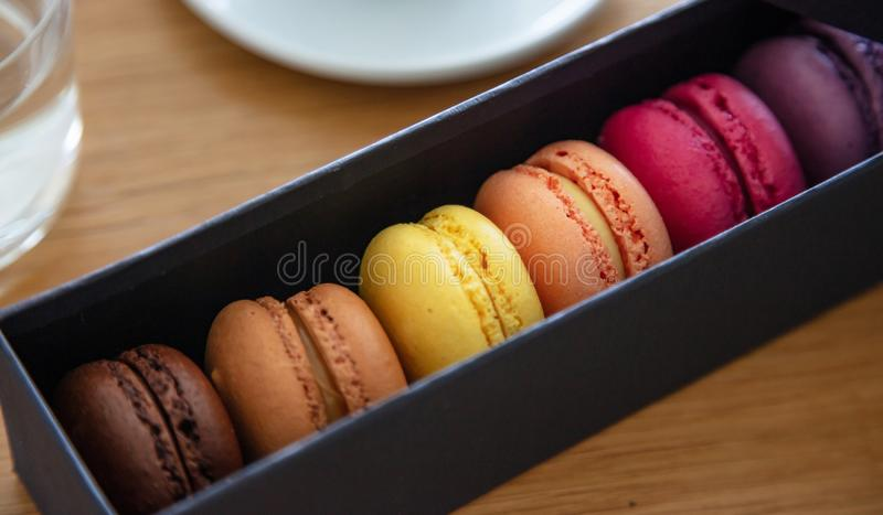 Colorful macarons in a black box, close up view. Macarons pastel colors in a black paper gift box, wood background, close up view with details royalty free stock photos