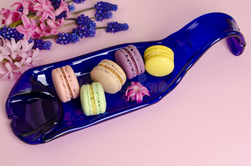 Colorful macarons on blue serving plate stock photography