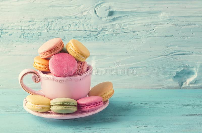 Colorful macarons in a cup. On a blue wooden background royalty free stock image